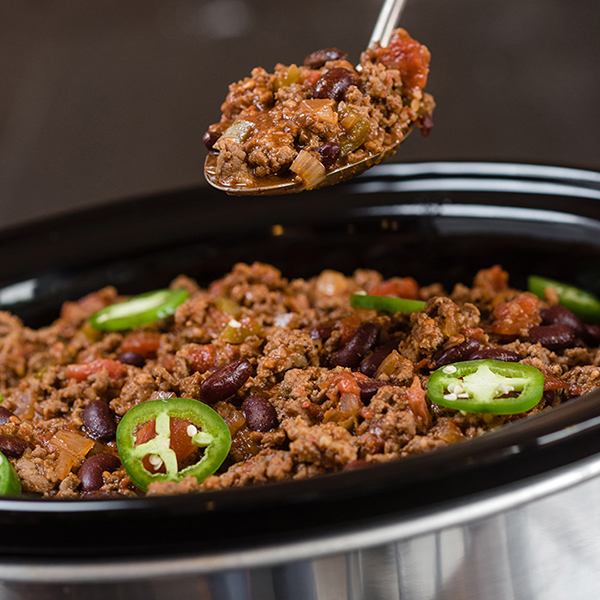 chili being spooned from a slow cooker