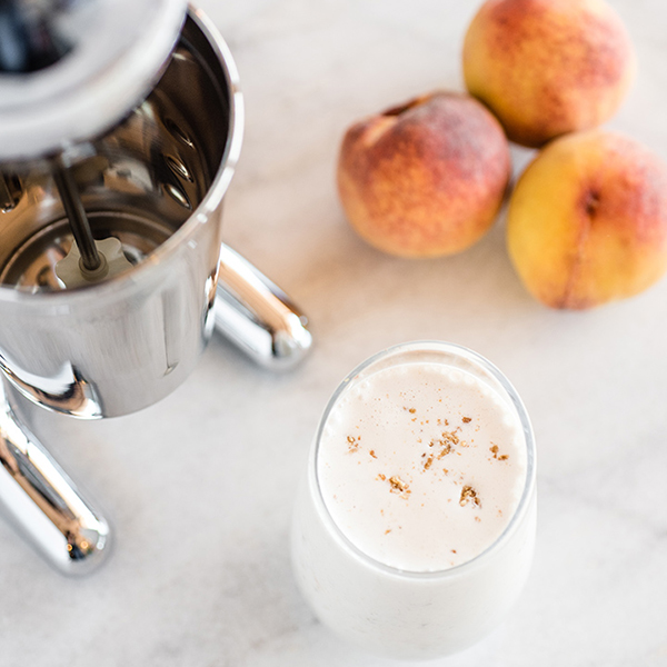 Peach Cobbler milkshake in a glass next to peaches