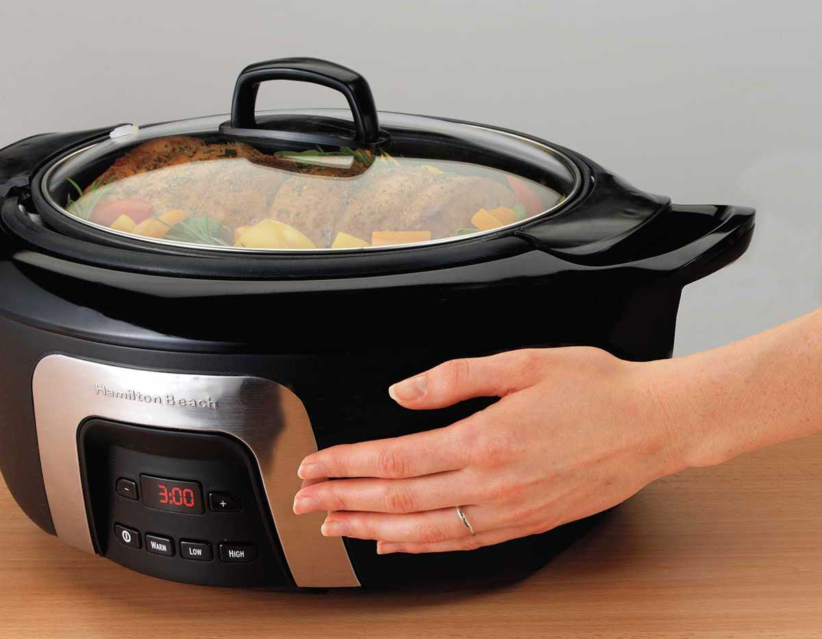 a hand touching the outside of a slow cooker