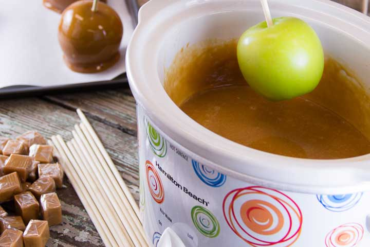 apple being dipped into caramel in a slow cooker