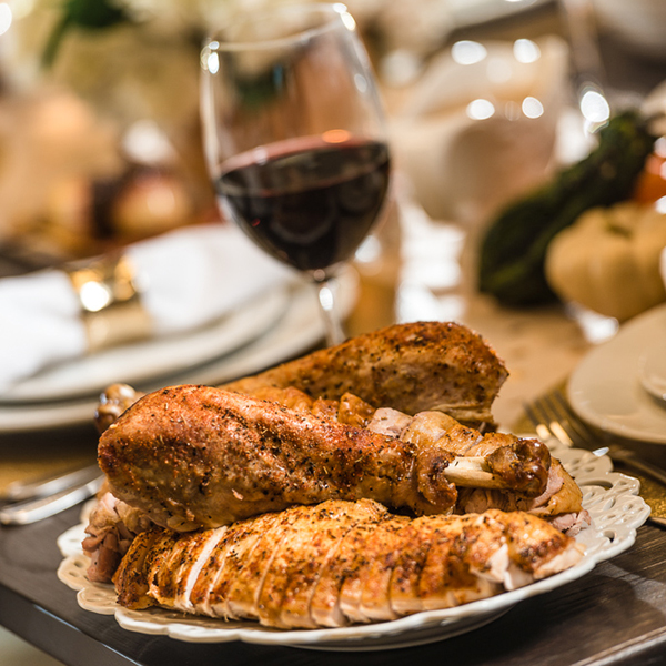 carved turkey on a plate with a glass of red wine