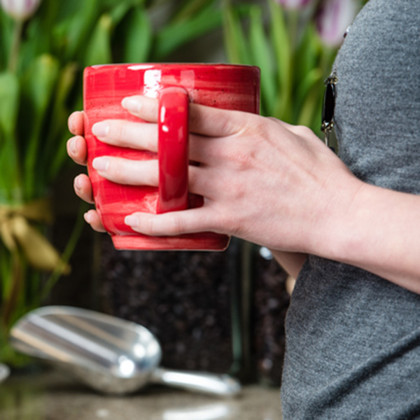 close up photo of a red coffee cup in hands