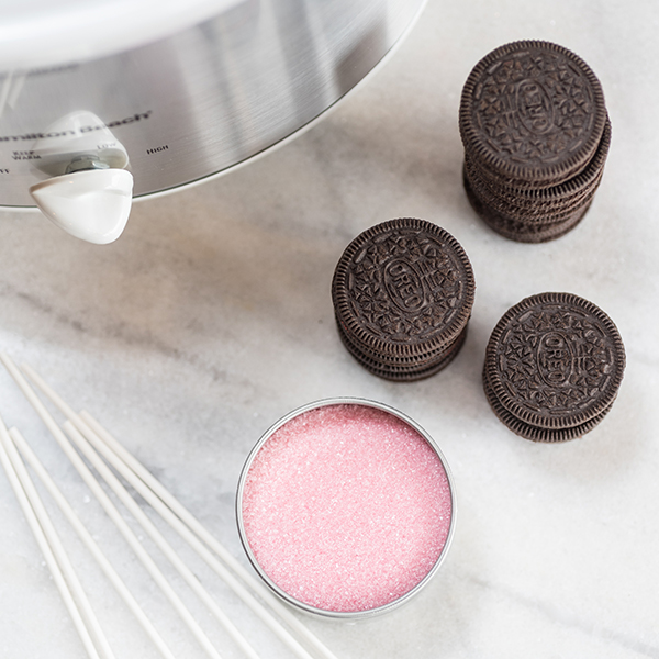 oreos, popsicle sticks, and pink sugar by a slow cooker