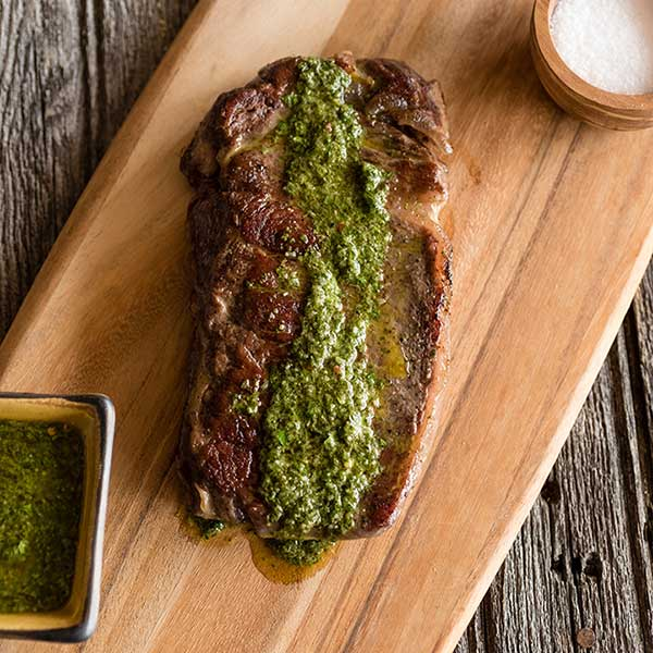 steak on a cutting board with pesto on top