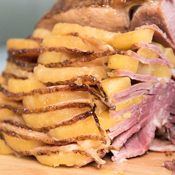 hasselback ham with pineapple slices on a cutting board